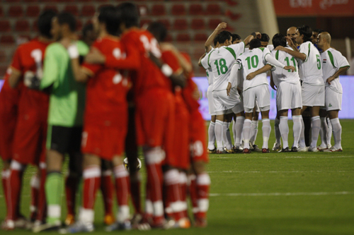 The Bahraini, in red, and Iraqi teams huddle before the game [AFP]