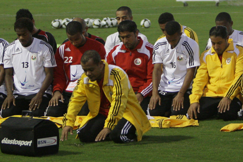 Omani players pray before a training session [AFP]