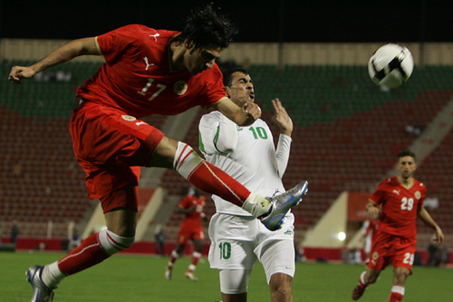 Iraq's Yunes Mahmud, right, feels the pressure from Hussein Ali Baba of Bahrain [AFP]