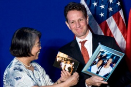 Geithner holds up a photo of him taken years ago during his studies at Peking University [AFP]