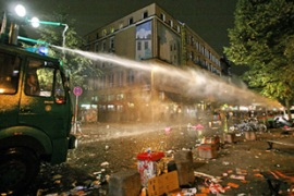 Police used water canons do disperse people throwing stones and setting cars on fire [EPA]