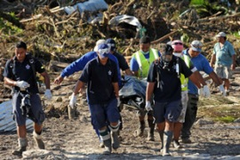 Rescue workers recover the body of a woman from the debris in Samoa [AFP]