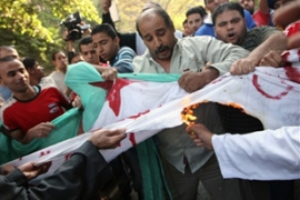 Egyptian protesters burn an Algerian flag during demonstrations after Egypt were knocked-out [AFP]