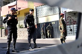 Soldiers and policemen stand guard outside the Brazilian Embassy where Zelaya is sheltering [AFP]