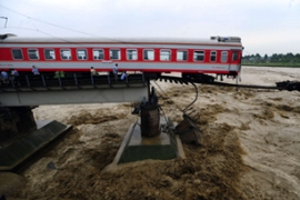In Sichuan province a train fell into a river after flooding destroyed a bridge [AFP]