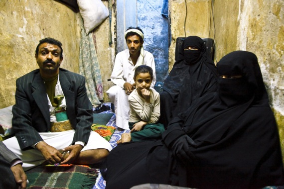 Twelve-year-old Sally Sabahi, far right, lives with her family in a single room tucked down a back alley of Old Sanaa.   Her father, far left, sells chili mix in the market for a dollar or two a day. Her mother, second from right, was married at 12, enduring five years of beatings before she finally divorced. [Credit: Hugh Macleod]
