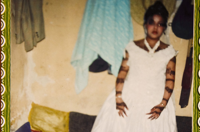 A picture of 10-year-old Sally trying on her wedding dress. Beaten, drugged and raped, Sally won a divorce from Nabil recently after her story made headlines in local media and became the focus of a national debate that has polarised Yemeni society. [Credit: Hugh Macleod]