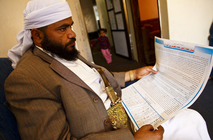 Sheikh Mohammed al-Hazmi inspects the fatwa, or religious ruling, he helped author which forbids any Yemeni from supporting a minimum age for marriage. [Credit: Hugh Macleod]
