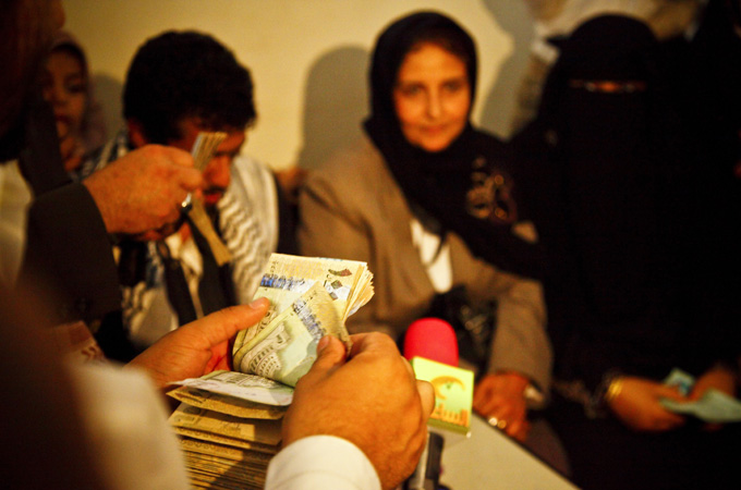 A clerk of the court counts the 200,000 Yemeni Rial dowry which had to be paid back to Nabil in order for Sally to divorce him. An American-Turkish woman offered to pay $700 after hearing about the case. The remaining $300 was donated by local Yemeni women. The divorce papers were signed by Judge Mansour Ali in the presence of Sally, her lawyer and Nabil. [Credit: Hugh Macleod]