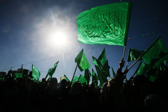 Palestinian supporters of Hamas wave flags during a rally marking the anniversary of the movement's foundation, in Gaza City [File: Ali Ali/EPA]