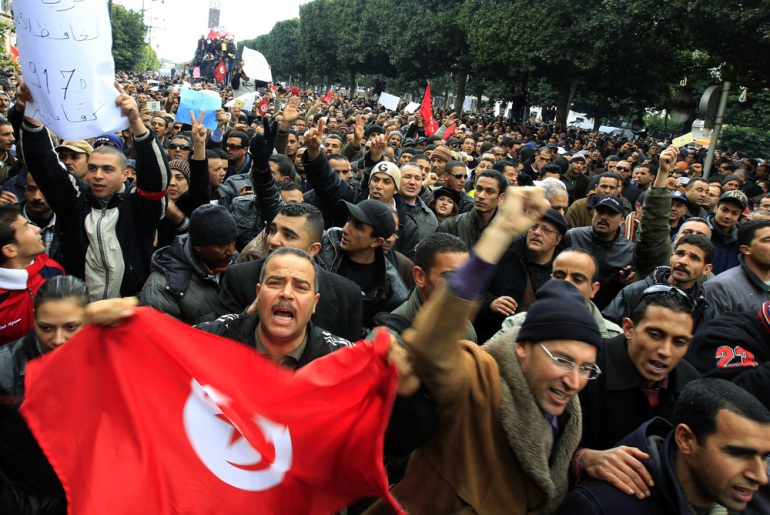 Thousands of protesters push past barricades and into a compound of government buildings in Tunis. They say they wil not leave until the interim government is dissolved [Reuters]