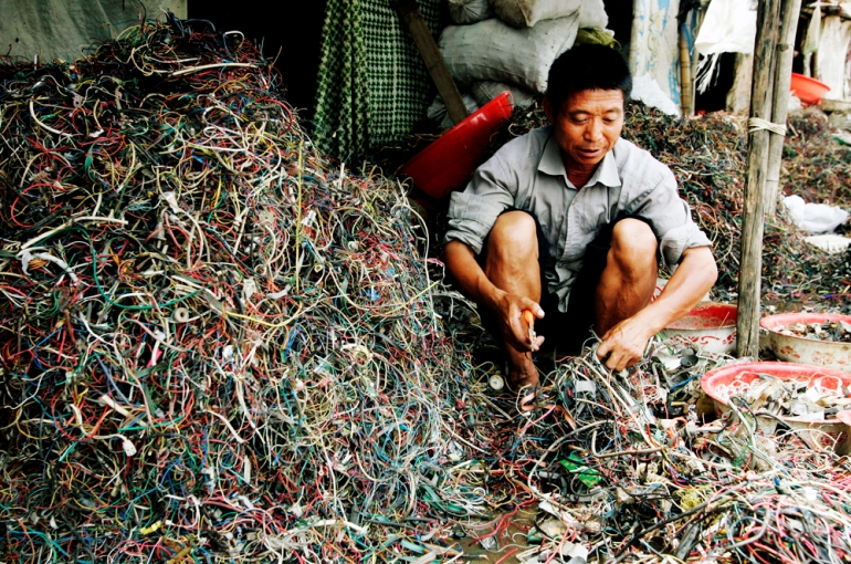 A worker rummages through e-waste for the purpose of salvaging metals and other materials for resale in Guiyu. E-waste is often illegally exported here from developed countries [EPA]