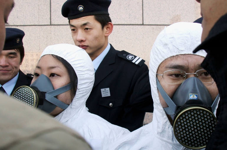 A Greenpeace activist is surrounded by security guards during a demonstration against e-waste outside the Hewlett Packard (HP) Beijing headquarters on December 7, 2005 in Beijing, China  [Getty]