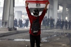 A protester holds up an Egyptian flag during clashes in Cairo January 28, 2011, [Reuters]
