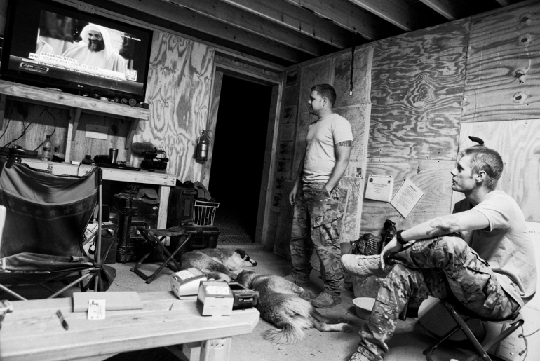US soldiers from 1 Platoon, Delta Co, 1-66, 4th Infantry Division, watch the news of Osama bin Laden(***)s death on TV at Combat Outpost TJ in the Arghandab Valley in Kandahar [John D McHugh]