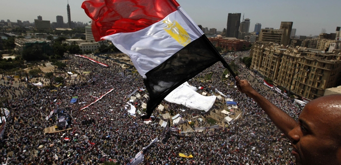 "An Egyptian waves a national flag as protesters gather in Tahrir square in Cairo July 8, 2011. Thousands of Egyptians gathered in Cairo""s Tahrir Square on Friday to demand faster reforms and the swifter prosecution of former officials from Hosni Mubarak""s toppled government who face corruption and murder charges. REUTERS/Mohamed Abd El-Ghany (EGYPT – Tags: CIVIL UNREST POLITICS)"