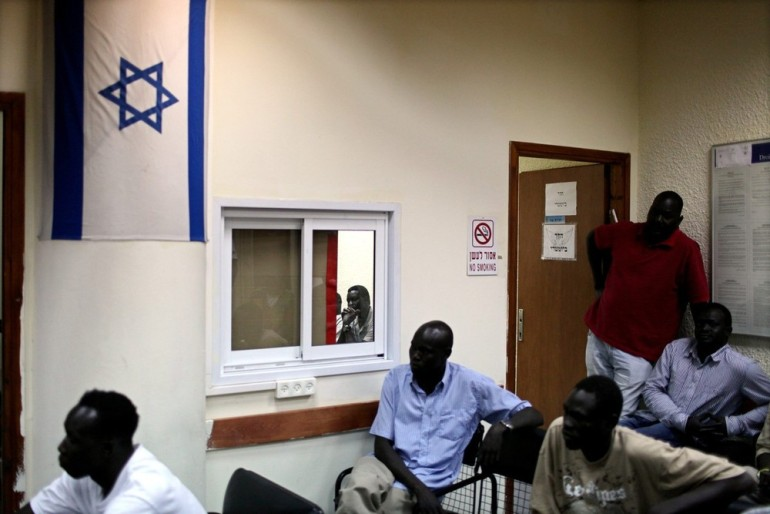 The migrants sit in a waiting room after being arrested in Holon near Tel Aviv.