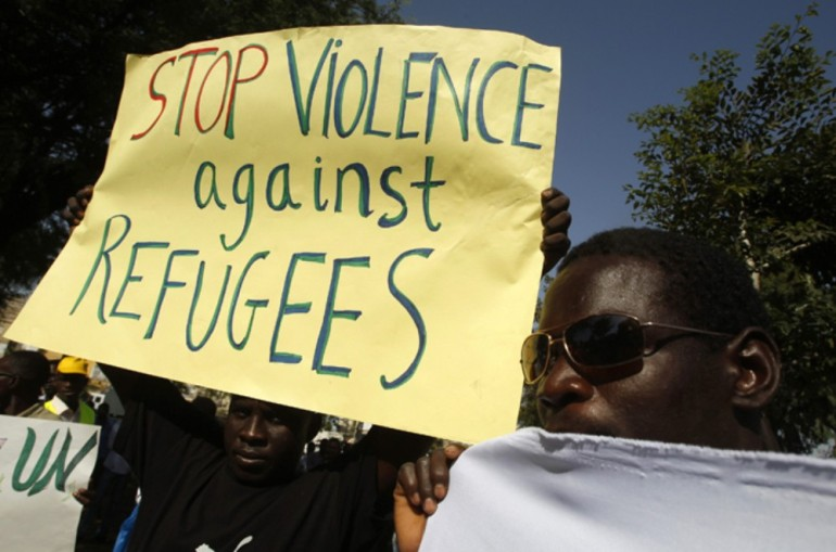 Sudanese protesters hold signs during a demonstration in Tel Aviv against the deportation of migrants from South Sudan.