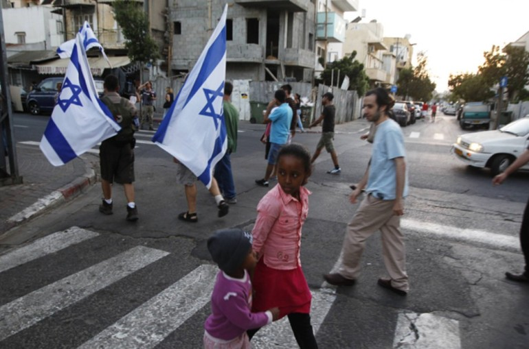 Children cross the street as residents of south Tel Aviv carry Israeli flags during a protest against African migrants living in their neighbourhoods.