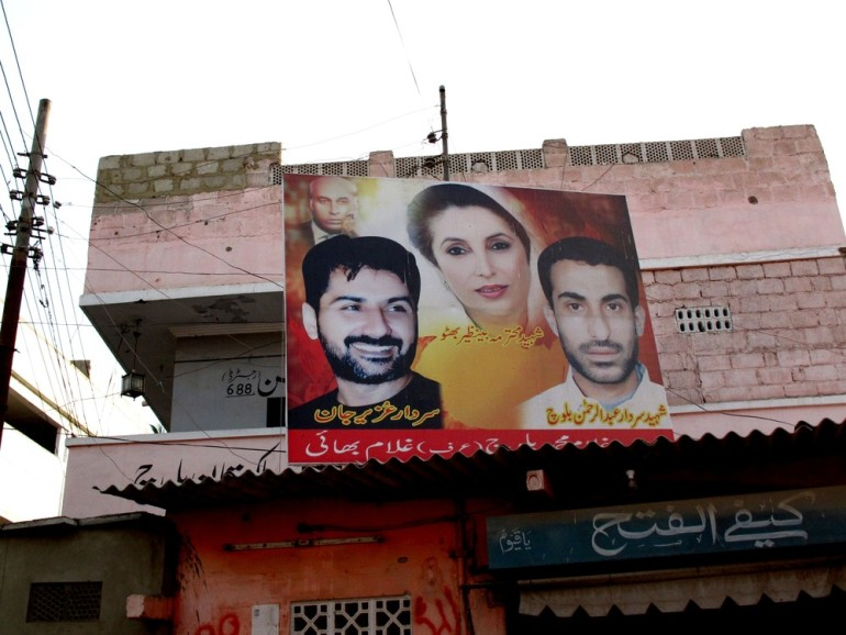 "This Pakistan People(***)s Party sign, in the crime-ridden Lyari neighbourhood, shows Uzair Baloch (left), Abdul Rehman Baloch (right) and former PPP chairperson and twice prime minister Benazir Bhutto (centre). The PPP has since disavowed both men, terming them ""gangsters"". Rehman was killed in a police ""encounter"" in 2009."