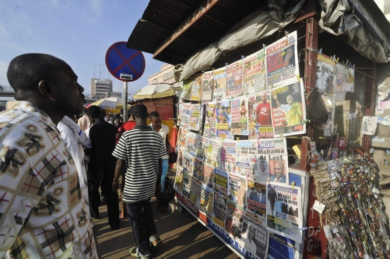 People read newspapers reporting the death of Ghana President John Atta Mills, 68, in Accra, on July 26. Vice President John Dramani Mahama was sworn in hours after the announcement of Mills(***) death from a sudden illness.