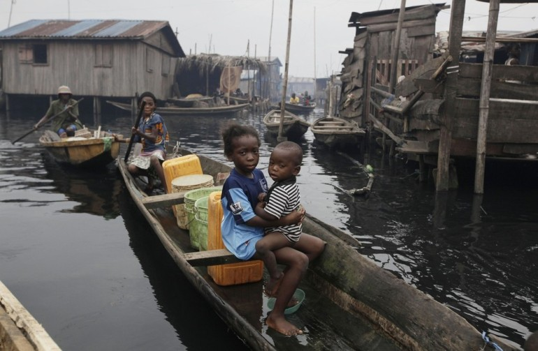 A woman paddles a canoe past stilt houses at Makoko, a floating slum in Lagos, Nigeria. A government-led eviction last week saw men in speedboats destroying homes with machetes, resulting in 3,000 newly homeless people.
