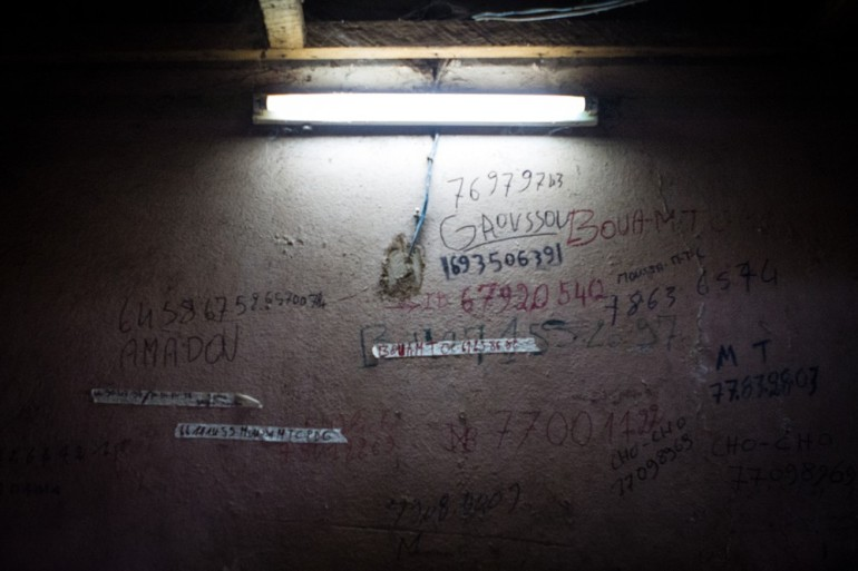 Phone numbers of northerners are scrawled on the wall at the bus station in Bamako.