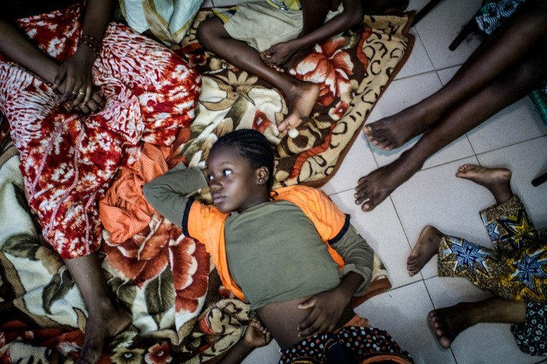 Aïcha Maiga, 12, sprawls out in the living room where she sleeps with 28 other family members.