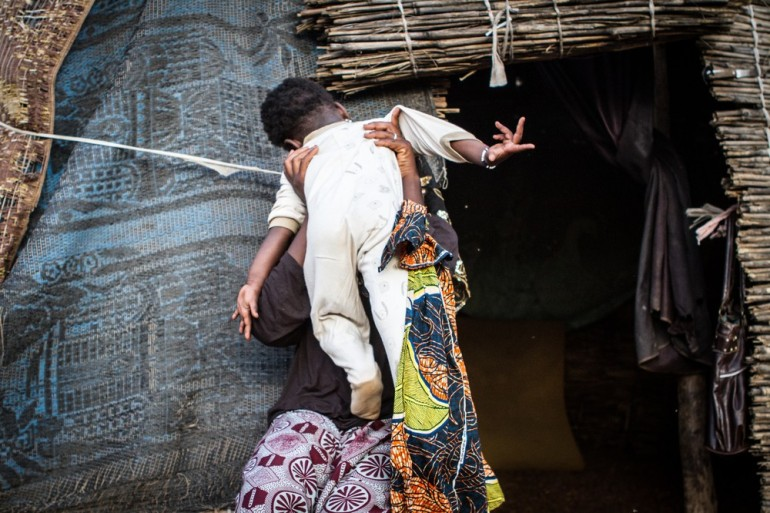 A Tuareg mother embraces her baby in front of a house her family has built on the outskirts of Bamako.
