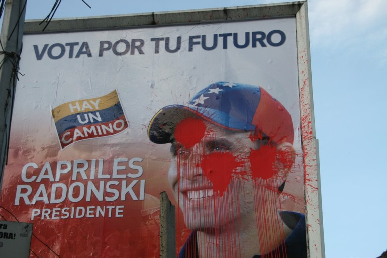 A poster supporting the Capriles is vandalised with paint bombs. The opposition complains of facing intimidation from government supporters.