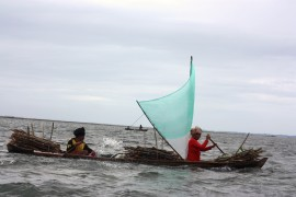 A firewood collecting team returning home in a traditional Bajau sampan. Duties are split. One steers while the other bails the boat.
