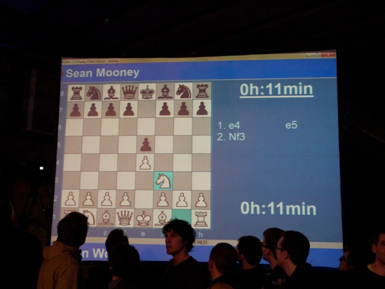 Large screens of the chess action show the crowd who is winning the four-minute speed-chess rounds. [Al Jazeera/Jack Hochschild]