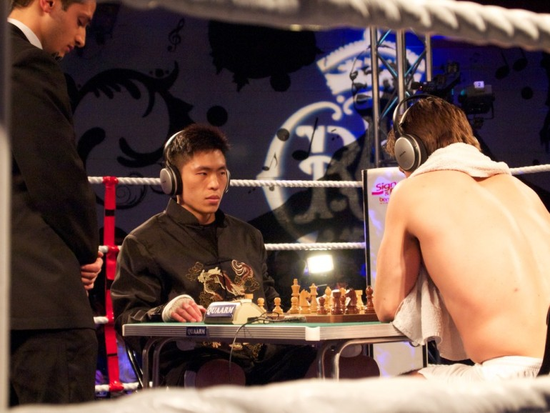 Bryan Woon faces off across the board against Mooney. The competitors wear headphones so they can(***)t hear the commentary on the game explaining the moves to the audience. [Al Jazeera/Jack Hochschild]