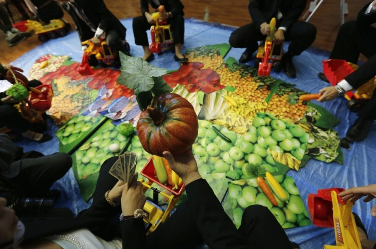 Activists in Tokyo, representing investors, hold out plastic vegetables as they ride toy excavators on a large map featuring pictures of food in the shape of the African continent during a protest against investors whom they claim are taking Africa(***)s land and food.