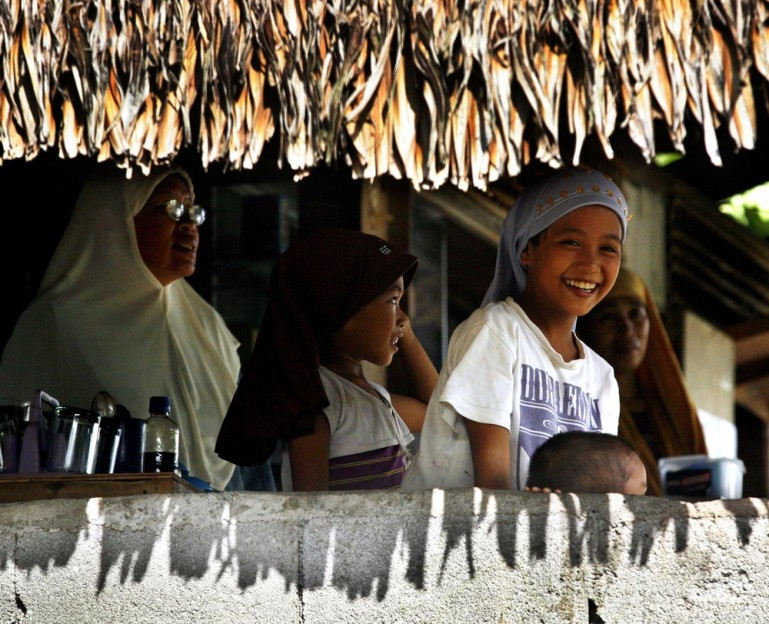 A girl smiles with other Filipino Muslims in a store on Mindanao.