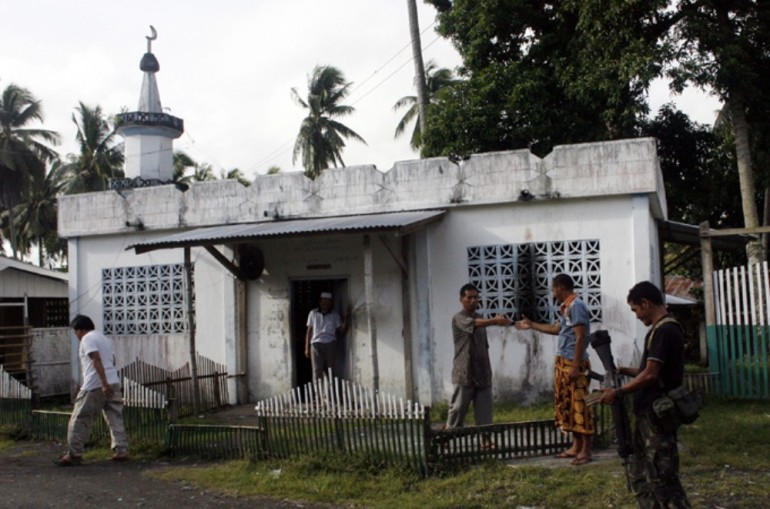 Members of the Moro Islamic Liberation Front pass a mosque as they patrol inside the rebel(***)s camp.
