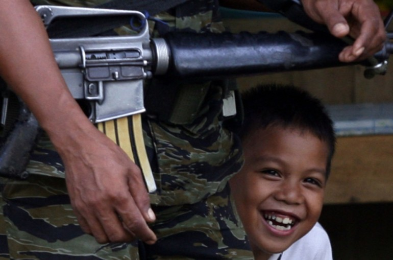A young boy hides behind a Muslim rebel inside Camp Darapanan on Mindanao island.