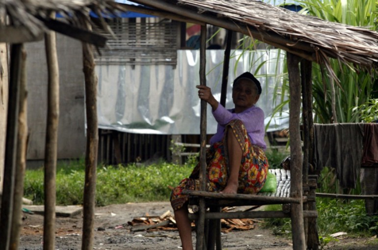 An old woman sits outside the evacuation centre where she has lived for two years.