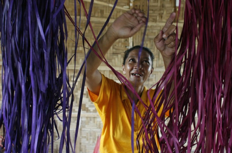 A displaced woman sorts out coloured grass she uses in weaving mats.