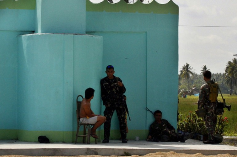 Government soldiers rest beside a mosque in Datu Salibo town on Mindanao island.