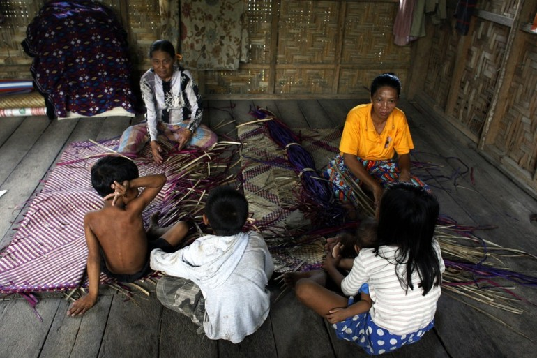 Women living in a centre for displaced people weave mats to earn a small income.