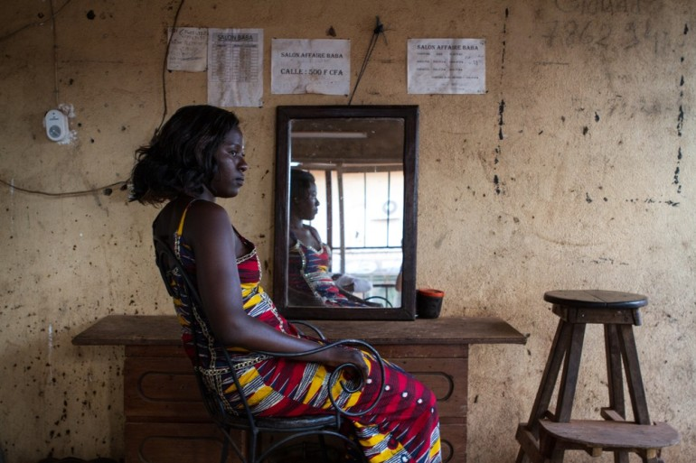 A woman relaxes in a simple hair salon in Bamako.