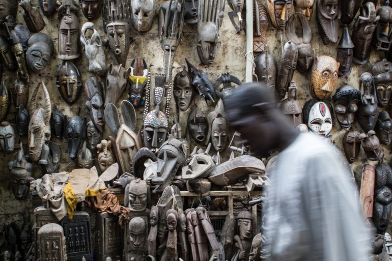 A mask seller walks past his display in the Grand Marché area of Bamako.