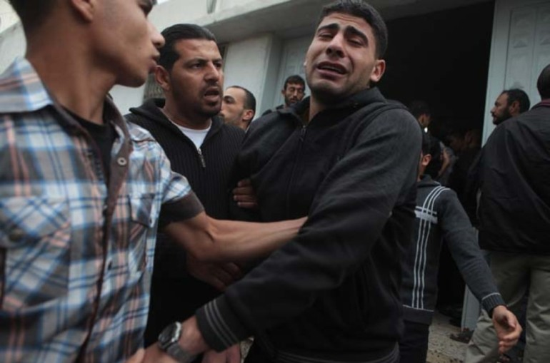 A relative of a Palestinian killed in Israeli attacks reacts at Shifa hospital in Gaza City.