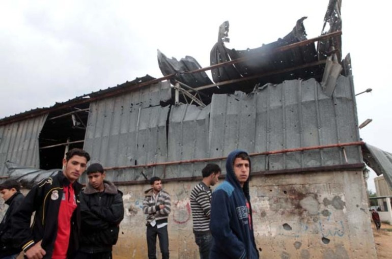 Palestinians gather in front of a damaged building.