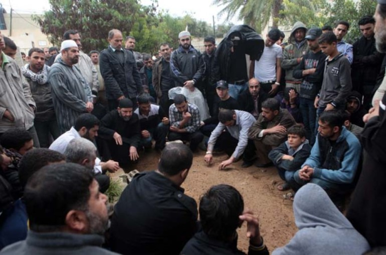 Men gather in a cemetery to mourn the death of one of the Palestinians killed the day before.
