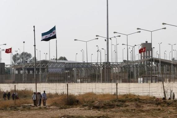 Syrians, with the damaged Tel Abyad customs office in the background, walk to Turkish side of the border [Reuters]