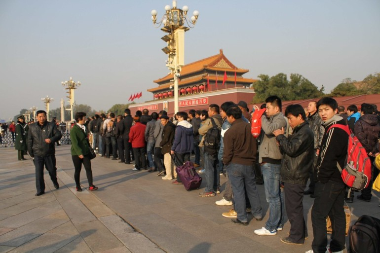 Citizens wait for security checks  in order to access the Tienanmen Square. Security measures have increased throughout Beijing while the National Congress has been taking place.