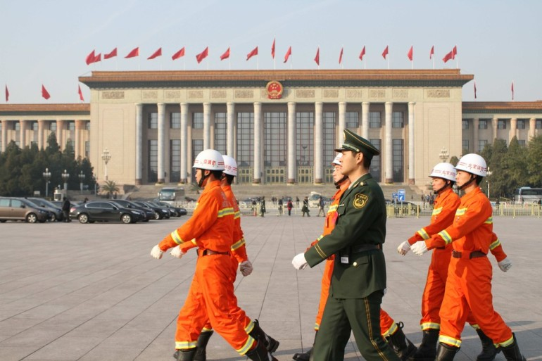 Chinese firemen walk in front of the Great Hall of the People to prevent Tibetans from self-immolating, an act often used to protest controversial Chinese control of the area.