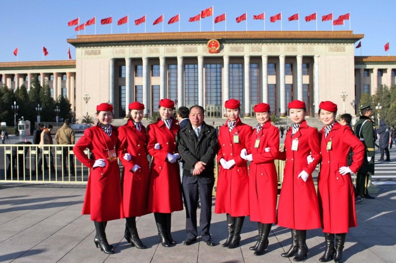 Congress hostesses pose with a guest for a photo in front of the Great Hall of the People, where the 18th Congress was held for over a week.